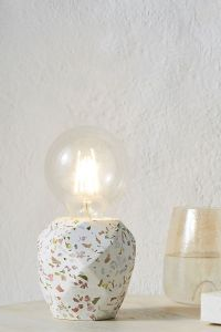 A medium-sized table-top lamp with a geometric, terrazzo base and large Edison-style light bulb.