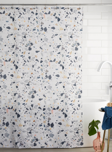 A cloth, terrazzo printed shower curtain is featured in a white bathroom.