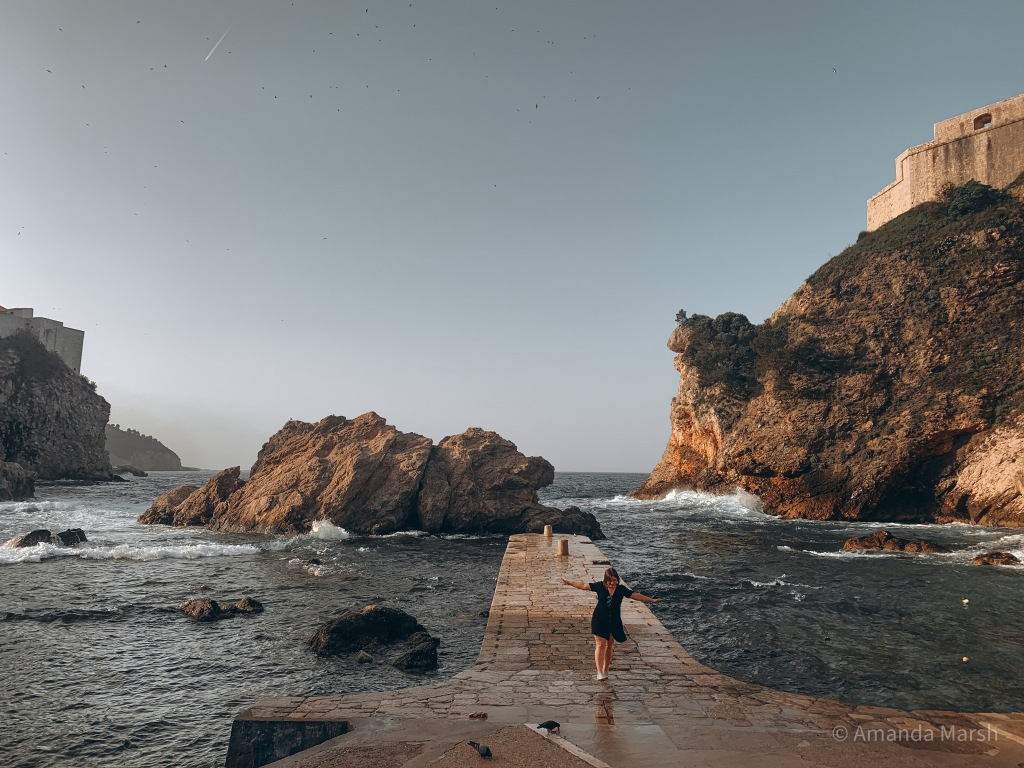 image of me, walking on a cement dock while sea waves crash, surrounded by towering cliffs.